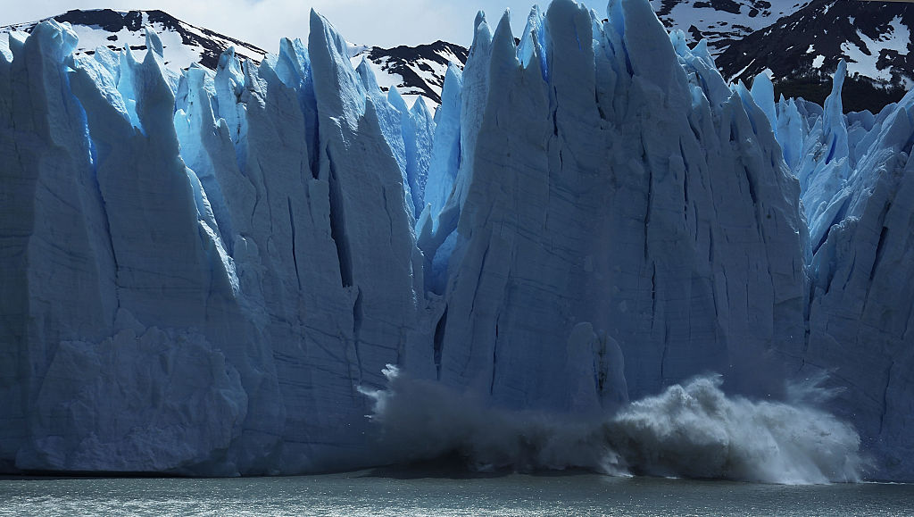 A giant spikey blue wall of glacial ice calves into the sea