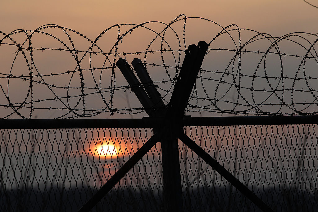 barbed wire and a wooden fence with a sunset behind it