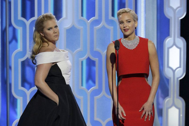 Amy Schumer and Jennifer Lawrence stand next to each other on stage