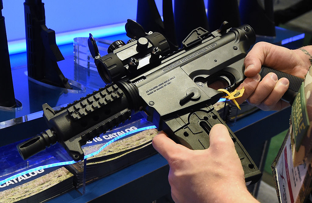a buyer looks at a semi-automatic gun