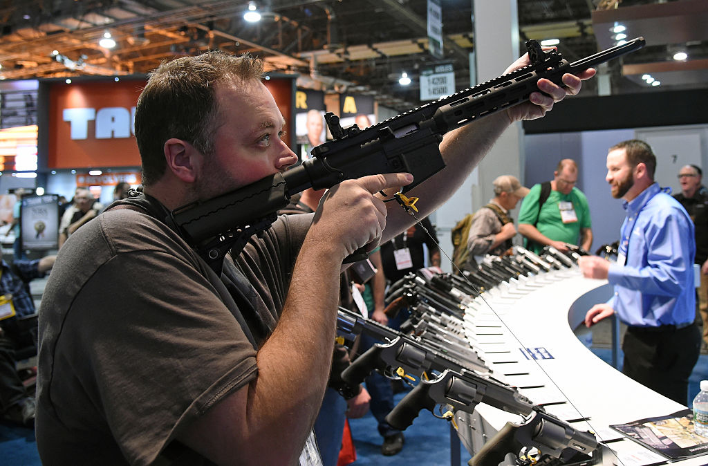 Man sighting a rifle at a gun show