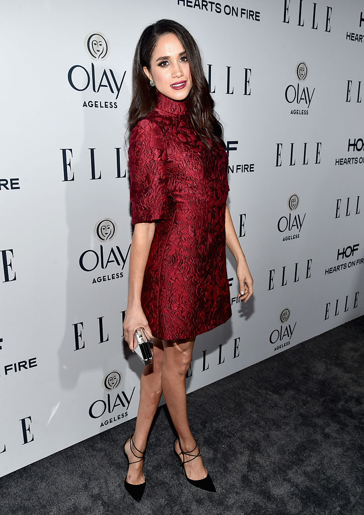 Meghan Markle posing in a red dress.