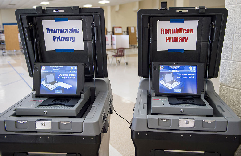two voting machines, one with Republican and one with Democrat signs on them