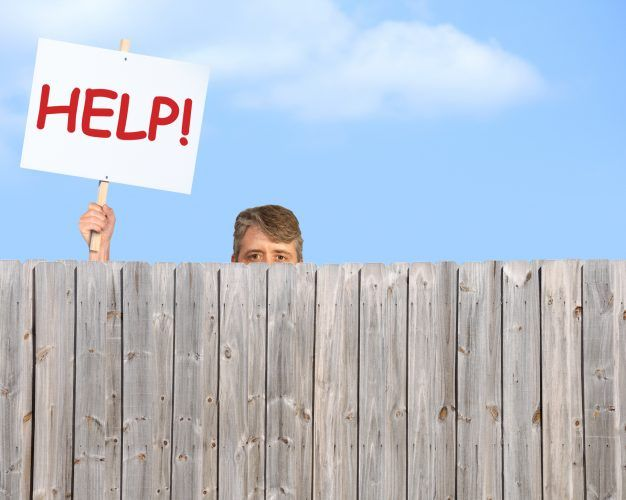 A man holding a HELP sign is peering over a fence desperate for help
