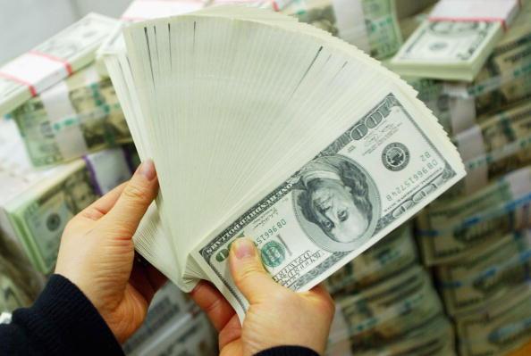 a fan of US 100 bills in hands