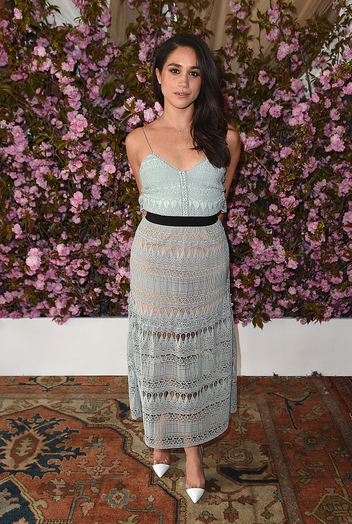 Meghan Markle poses on an intricate rug in a crochet dress in front of flowers