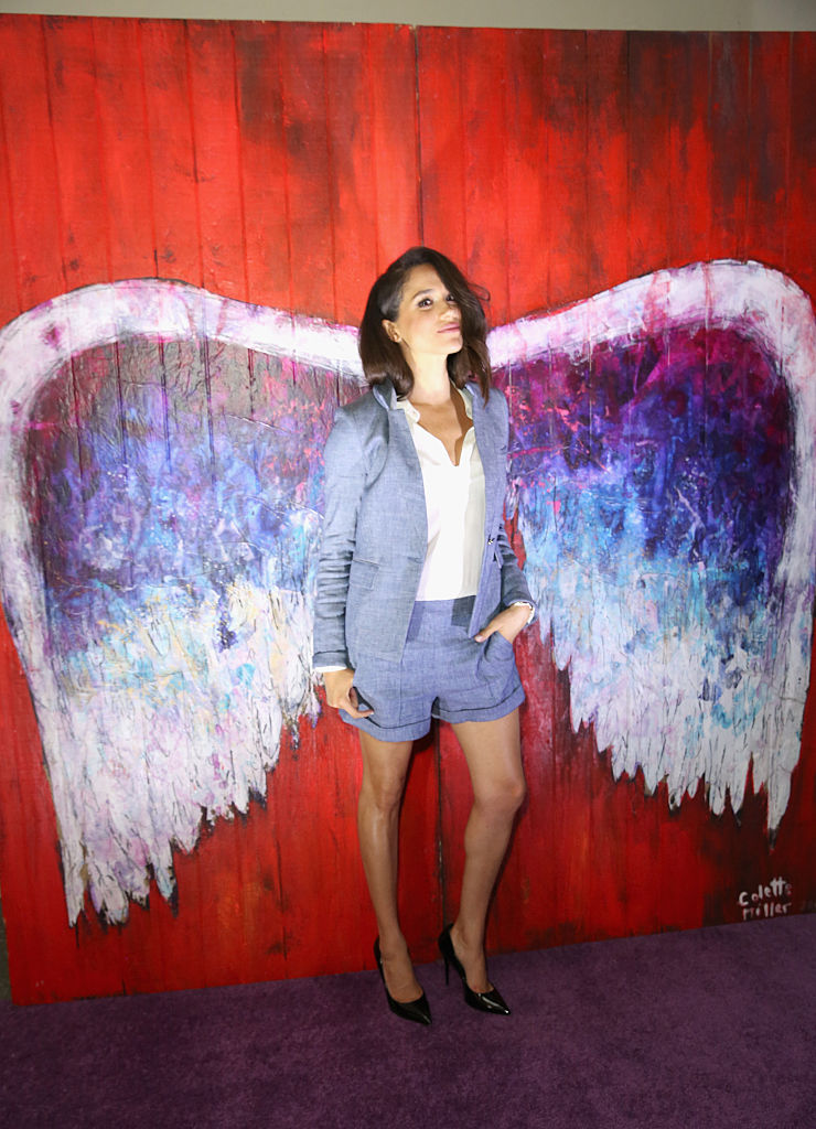 Meghan Markle posing in front of a red wall with painted wings on it.