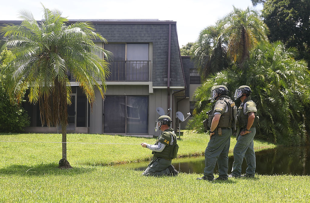 a bomb squad in green fatigues outside a gray apartment building with green grass and palm trees