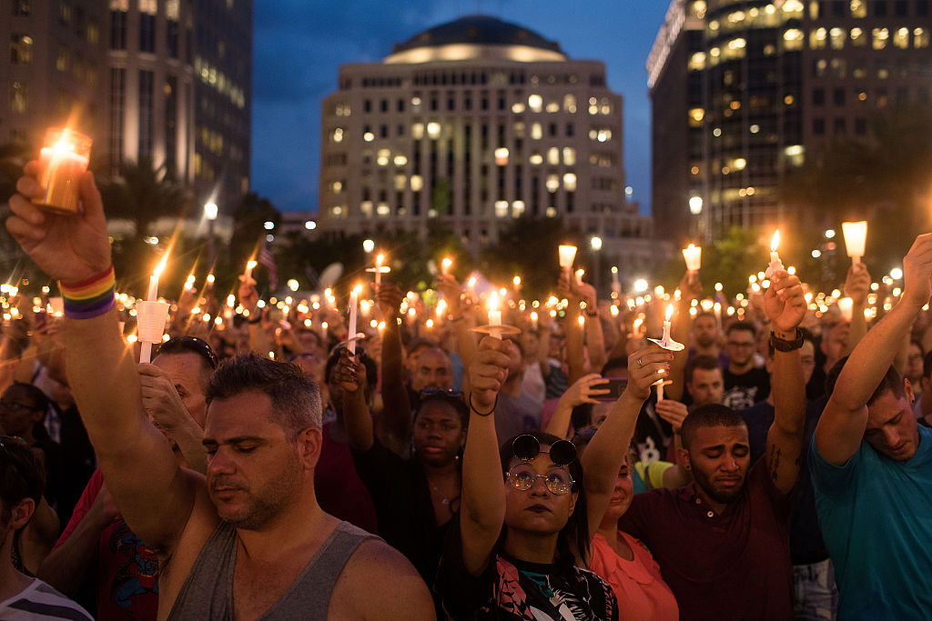 People hold candles during an evening memorial service for the victims of the Pulse Nightclub shootings, at the Dr. Phillips Center for the Performing Arts