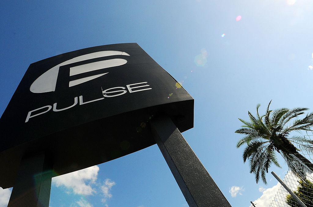 the black and white sign outside Pulse Nightclub against a blue sky and a palm tree