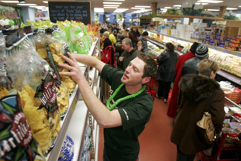 Jason Baglin restocks chips as shoppers line up inside Trader Joe's for the grand opening on 14th Street on March 17, 2006 in New York City. Trader Joe's, a specialty retail grocery store, has more than 200 stores in 19 states. (Photo by Michael Nagle/Getty Images)