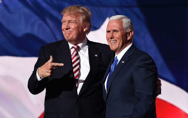 Donald Trump in a dark suit pointing at Mike Pence, also in a dark suit