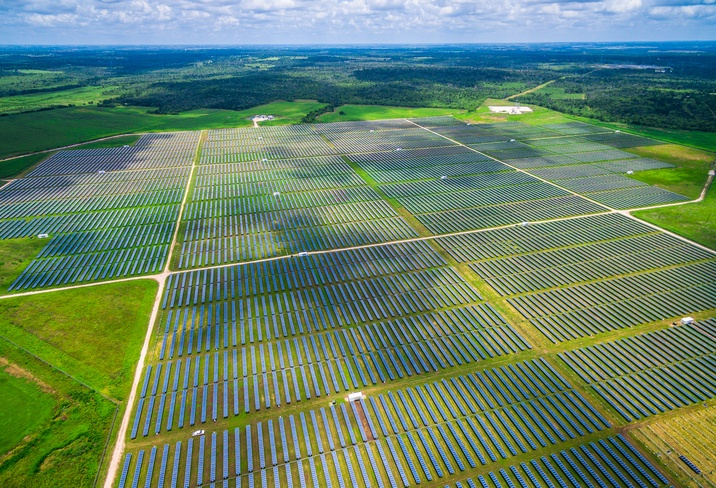 A large solar array over green fields with a blue sky
