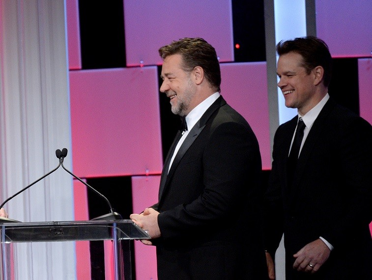 Russell Crowe and Matt Damon walk onstage together in suits