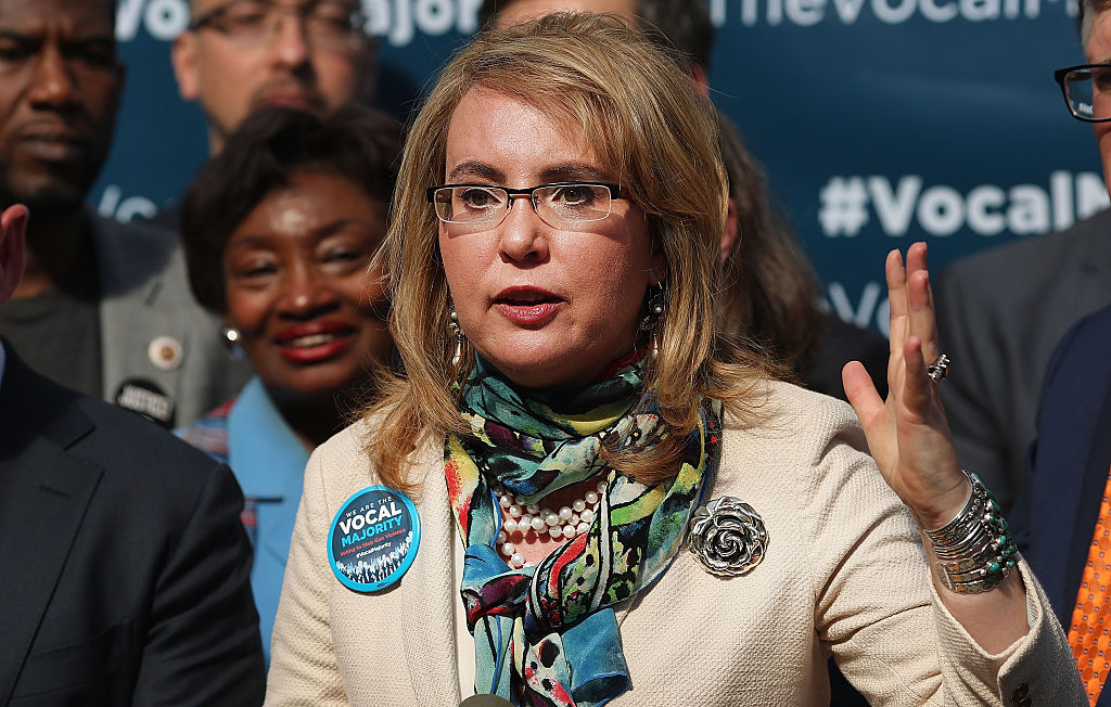 Gabby Giffords in glasses, a tan jacket, and colorful scarf