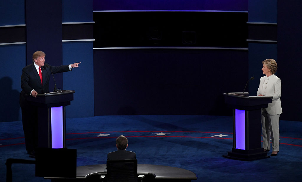 Donald Trump points at Hillary Clinton onstage in white at the last debate, in a dark room