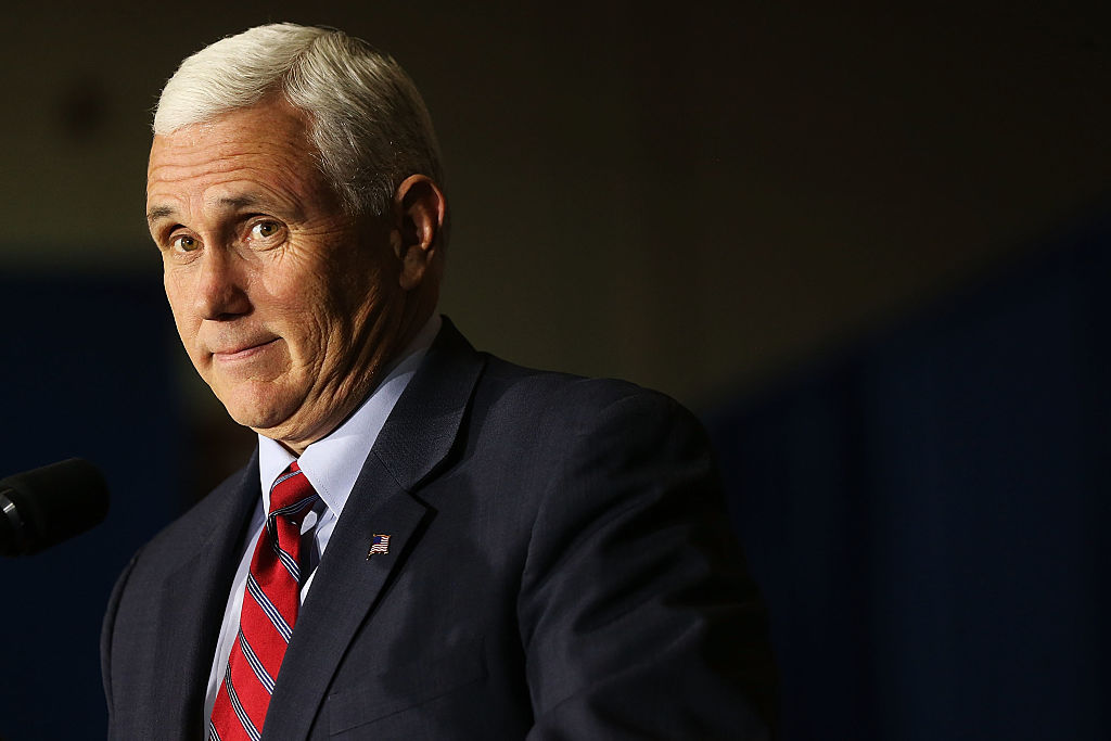 Mike Pence in a dark suit and red tie on a dark background