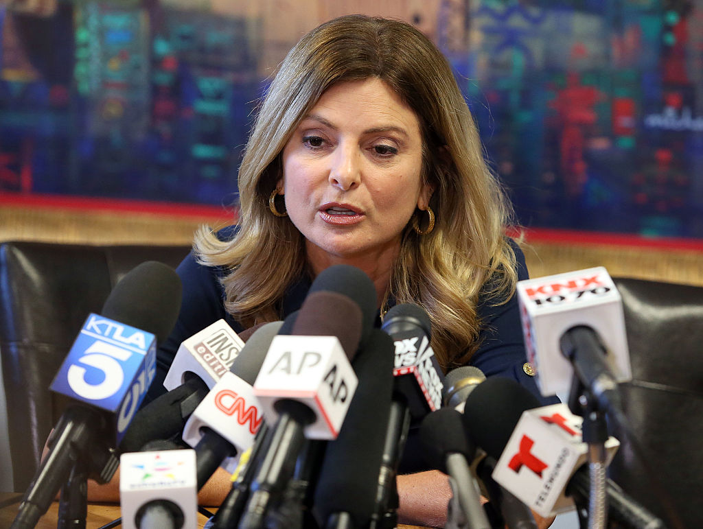 Lisa Bloom speaks into a cluster of microphones