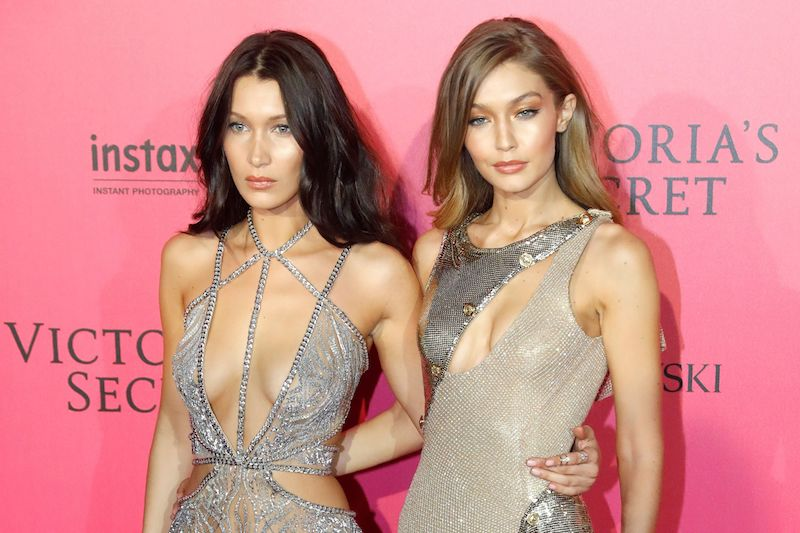 US models Bella Hadid (L) and Gigi Hadid pose during a photocall after taking part in the 2016 Victoria's Secret Fashion Show