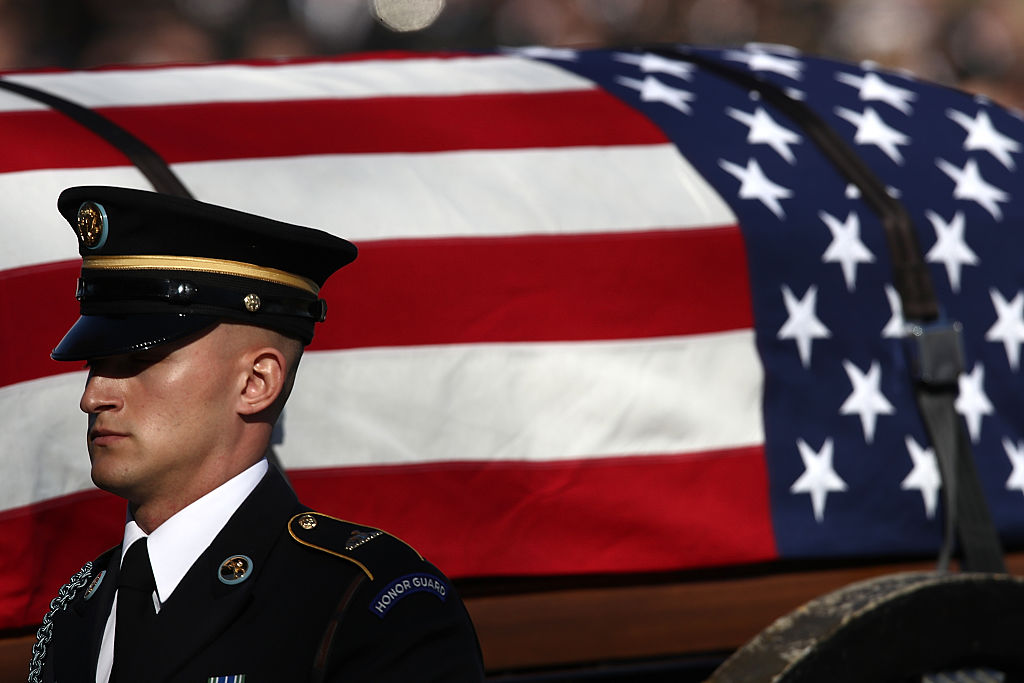 a military casket draped in a flag