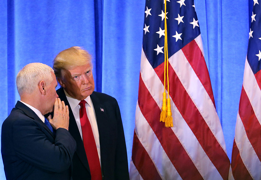 Donald Trump and Mike Pence whispering near an American flag