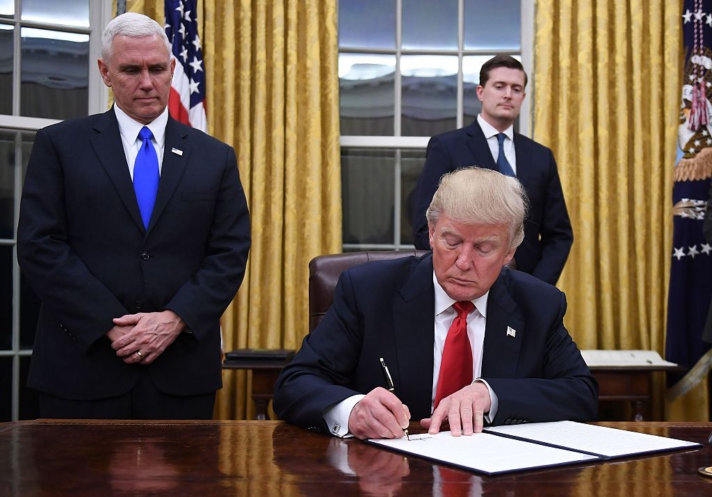 Donald Trump wearing a red tie and a dark suit signs a paper sitting at his desk