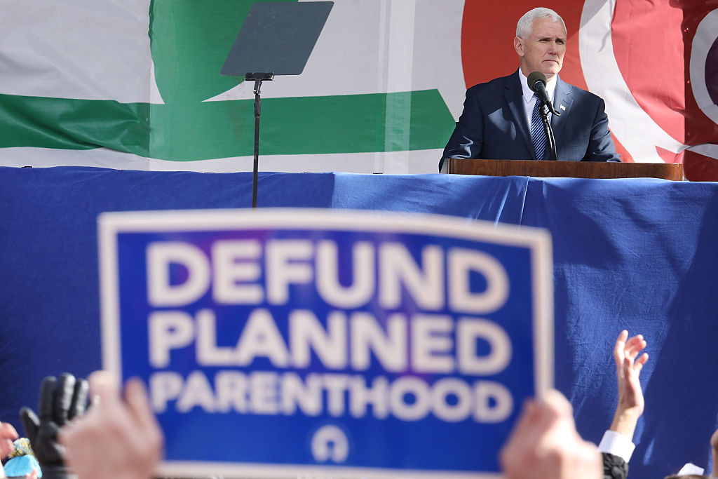 Mike Pence speaking with a blue and white defund planned parenthood sign in the foreground