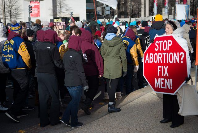 """A pro-choice advocate (R) holds up a red stop sign that says """"Stop Abortions Fix Men as pro-life demonstrators march towards the US Supreme Court"""