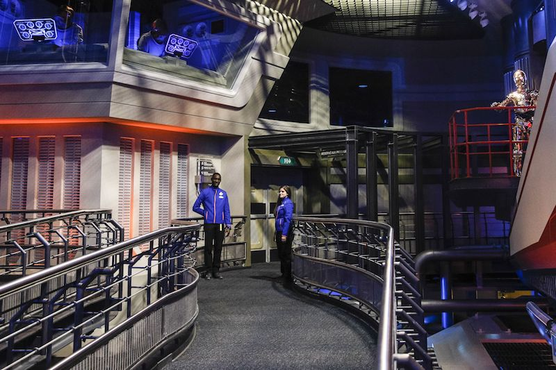 Two employees stand in a hallway at Star Tours The Adventure Continues
