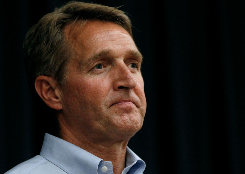 Jeff Flake tight, in a blue shirt, against a dark background
