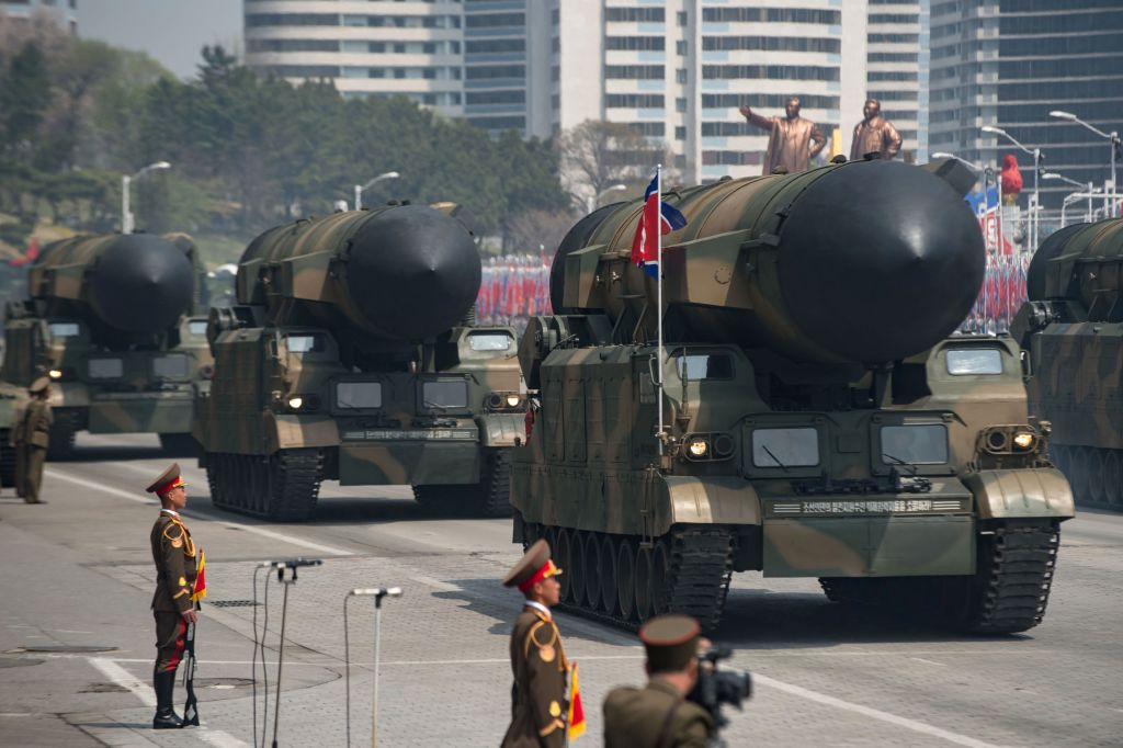 To large missile launch vehicles are paraded down the street in PyongYang