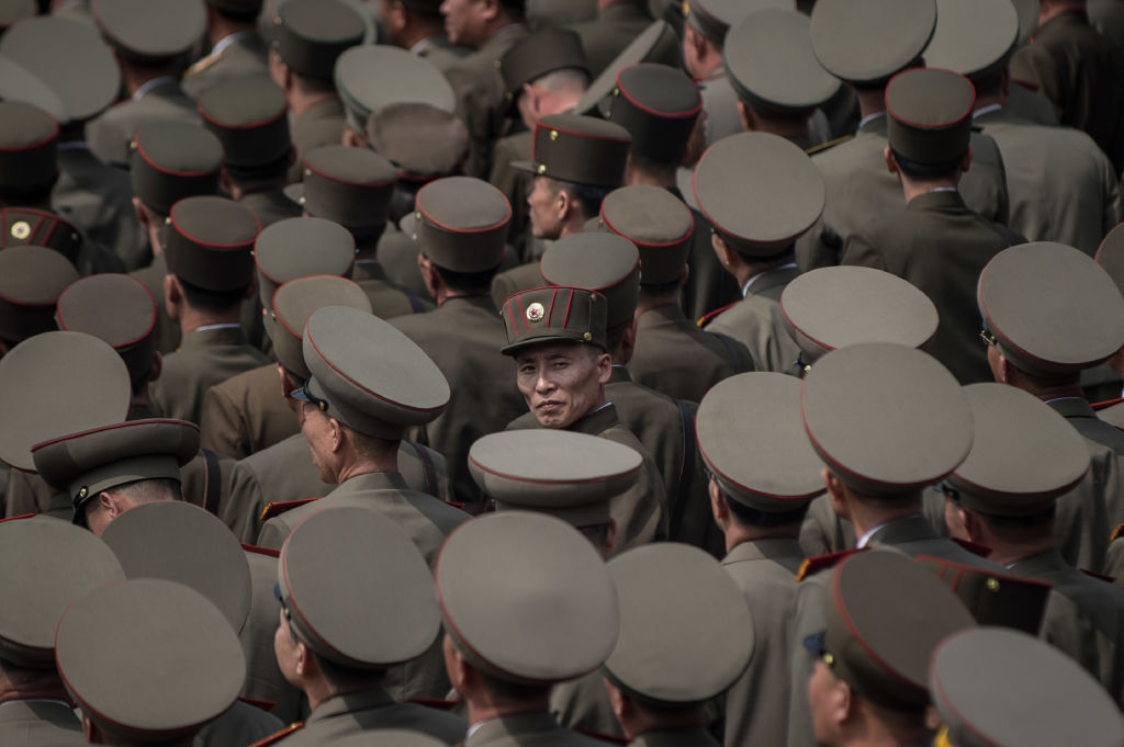a sea of North Korean army members in gray hats from the air