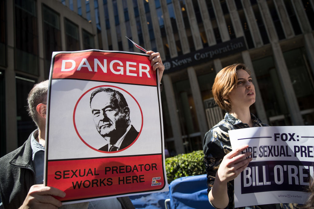 protestors outside Fox News holding signs with Bill Oreilly on them