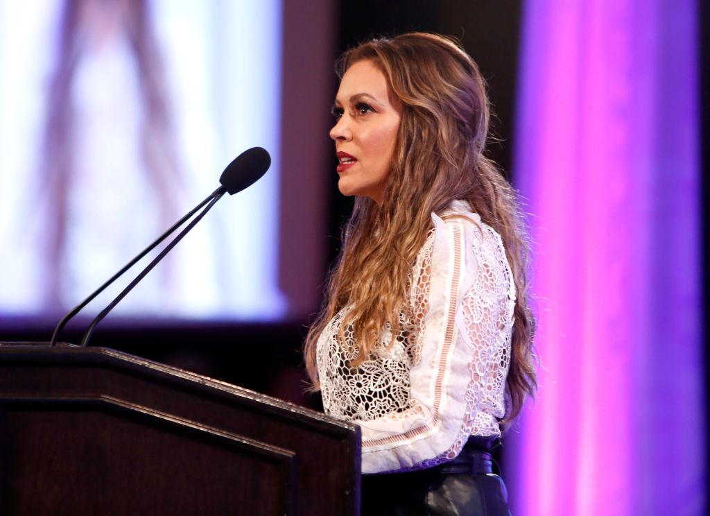 Alyssa milano in white lace at a podium on a purple background