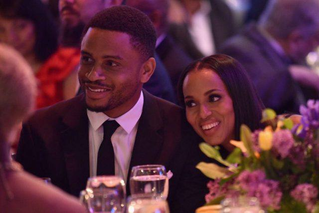 Nnamdi Asomugha and Kerry Washington smile and speak to other guests at a dinner table.
