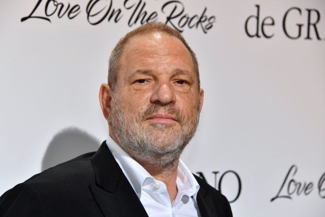 Harvey Weinstein in a dark suit and white shirt against a white and black background