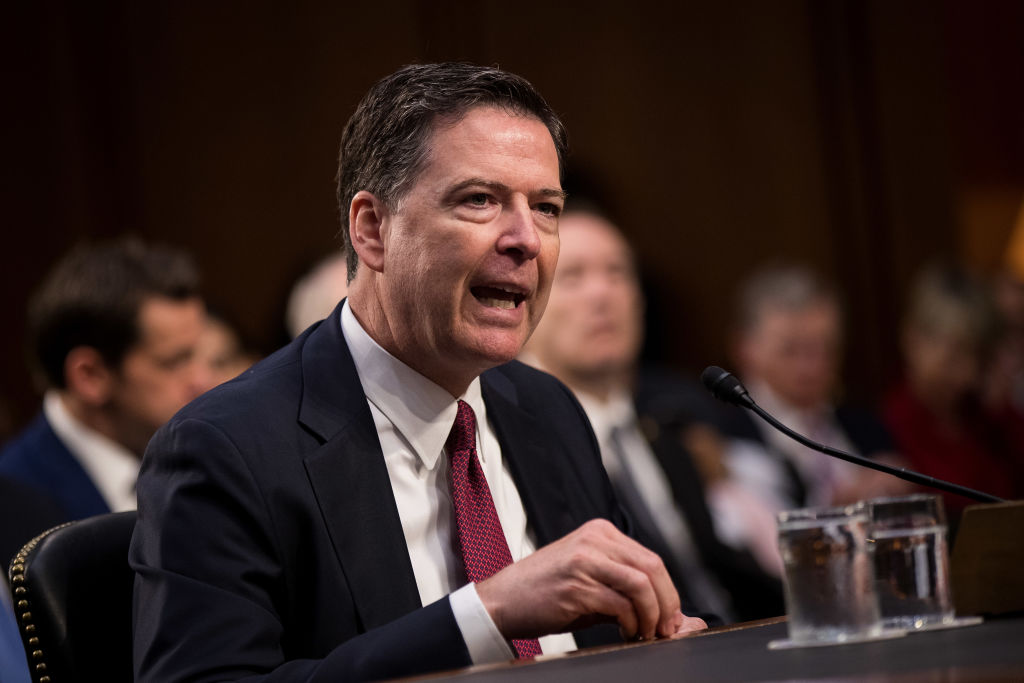 James Comey testifying in a dark suit and a red tie