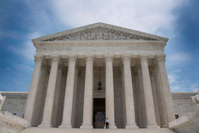 A police officer stands guard on the steps of the US Supreme Court in Washington, DC on a partly cloudy day