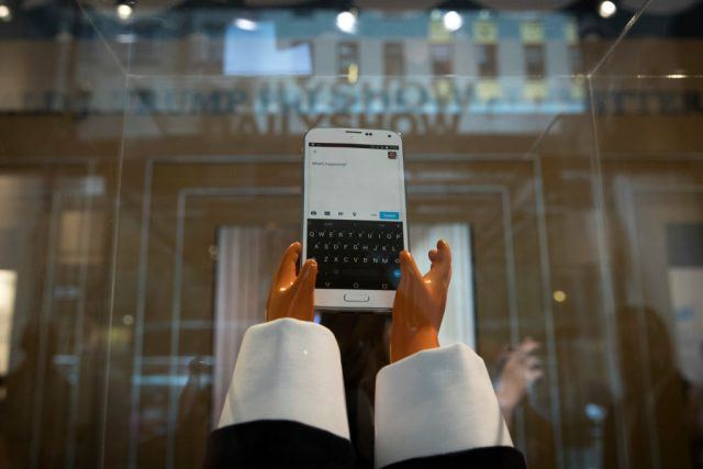 A parody of president trump's small hands tweeting on a blackberry phone displayed as a historical piece in the Presidential Twitter library