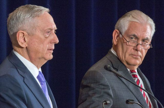 Secretary of state Rex Tillerson stands at a podium looking longingly to his right at Secretary of Defense General Jim Mattis