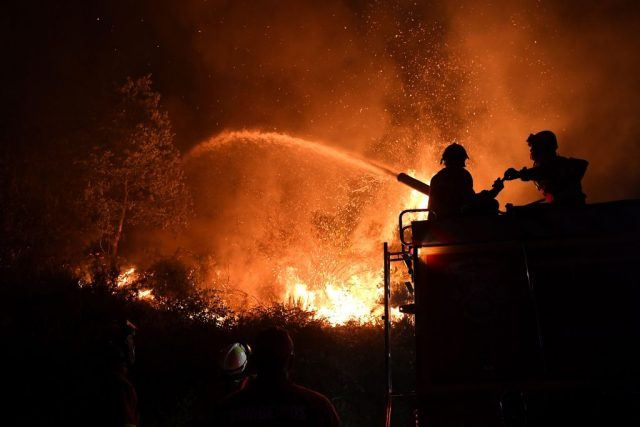 A firefighter in silhouette puts out a forest fire with a hose.