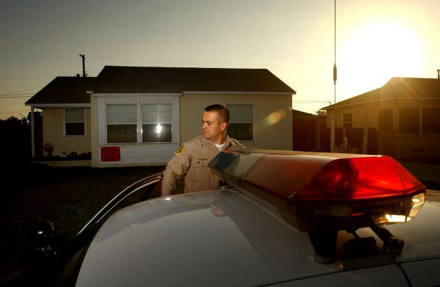 An officer stands in front of his patrol cruiser around sunset in front of a house