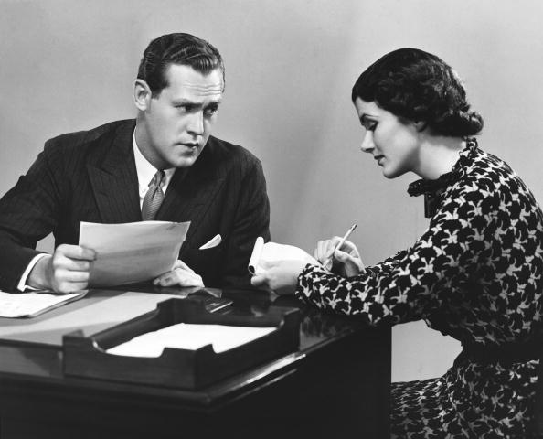 a black and white photo of a businessman with a secretary at a desk