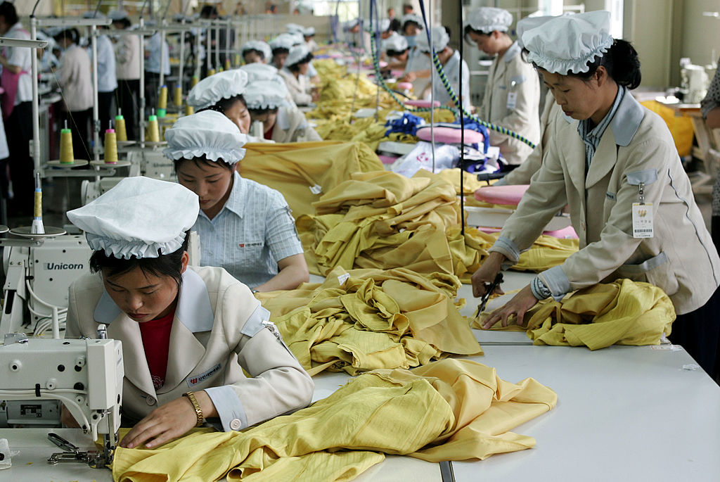 women in white work on yellow fabric in an assembly line