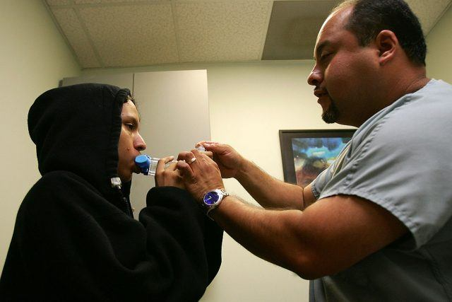 Asthma program director Alex Aldrete teaches 15-year-old Jesus Ayala the proper use of the new albuterol sulphate inhaler through a holding chamber at the Venice Family Clinic.