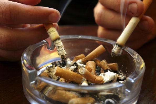 An ashtray full of cigarette butts. Two hands are seen holding cigarettes.