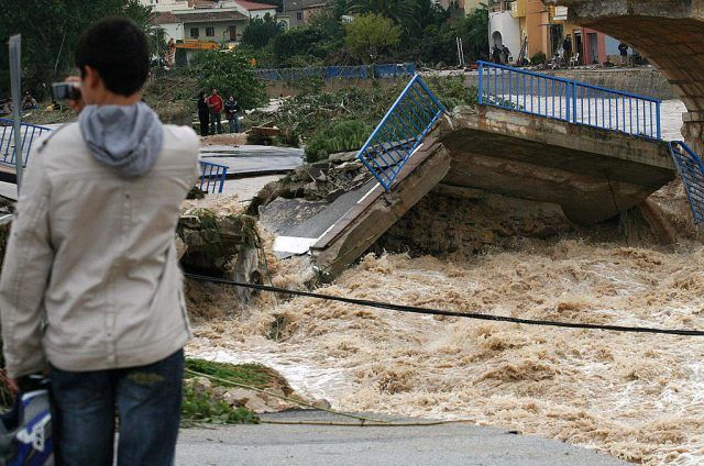 A man looks at a bridge destroyed by flooding.