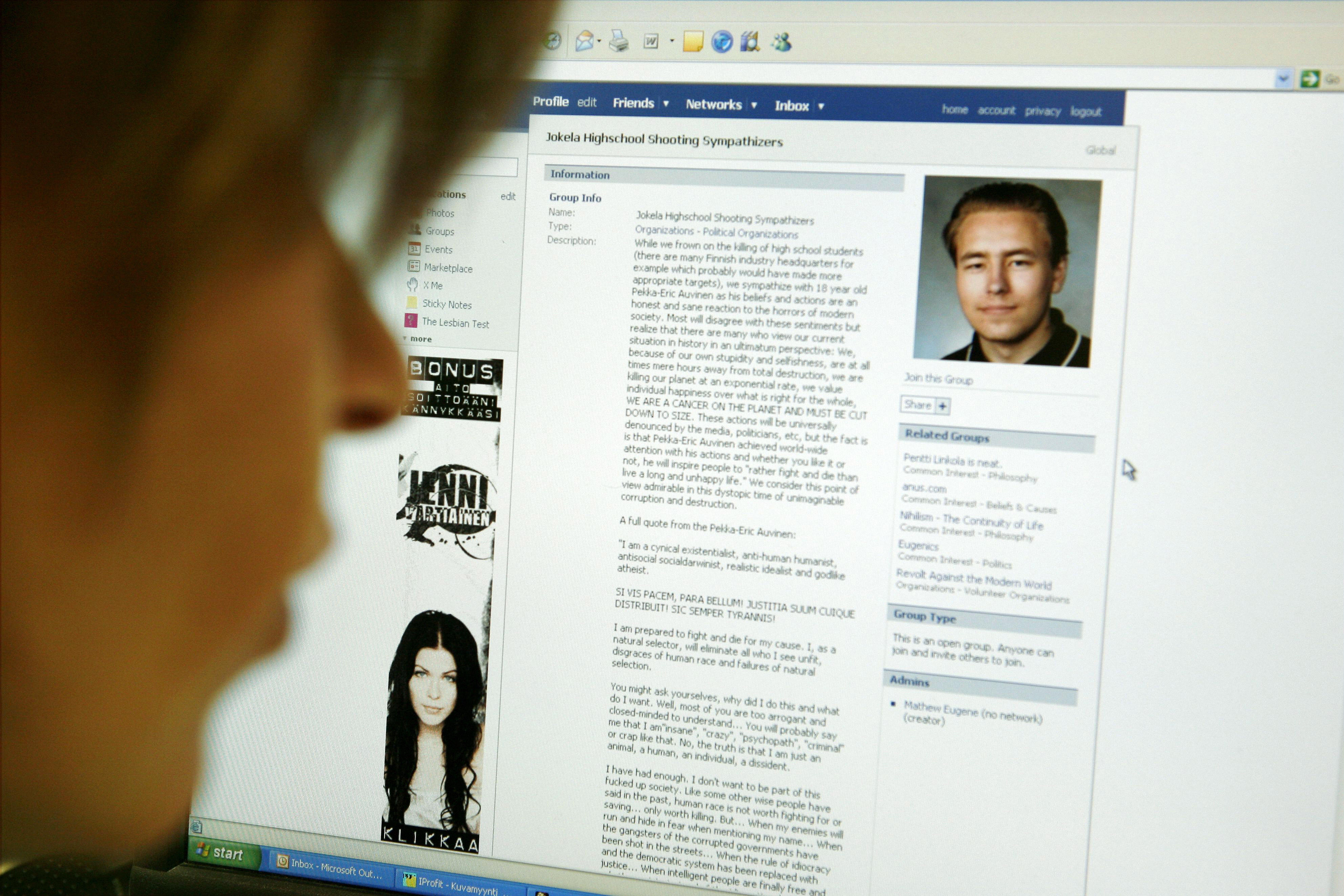 """A woman looks at an internet webpage of the """"Jokela Highschool Shooting Sympathizers' portraying a picture of Finnish high school student Pekka-Eric Auvinen"""