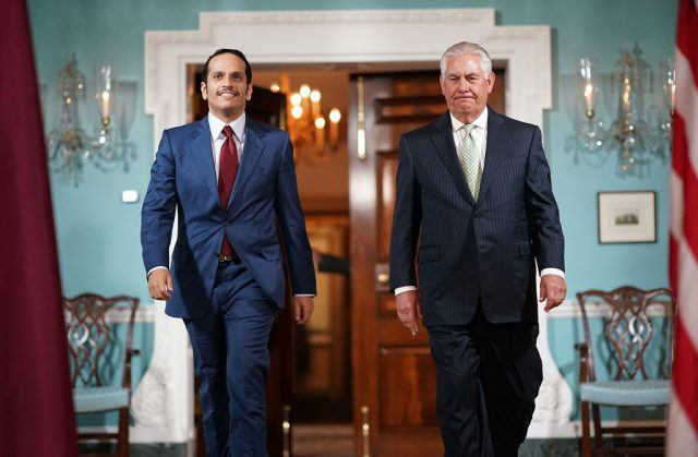 U.S. Secretary of State Rex Tillerson (R) escorts Qatari Foreign Minister Sheikh Mohammed Bin Abdulrahman Al Thani (L) through a lavish room in blue and white with a double door ajar in the backround