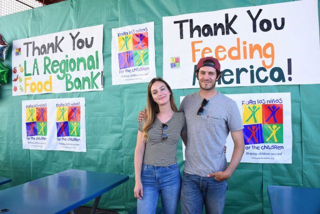 Leighton Meester and Adam Brody posing while attending a charity event.